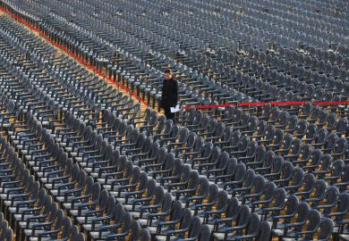 Person standing amongst empty seats as a metaphor for Concerns have been raised about the viability of some South Korean universities reported a record-high number of vacancies.