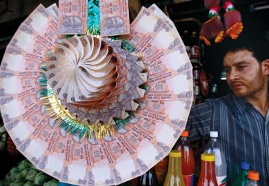 Salaries the priority as India mulls role of new research funder_A shopkeeper displays a garland made of Indian currency notes at a market in Srinagar.