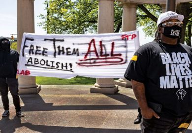 Black Lives Matter activist stands in front of other activists that advocate for abolishing the police during a rally against police brutality in front of the Columbus City Hall in Columbus, Ohio on May 1, 2021
