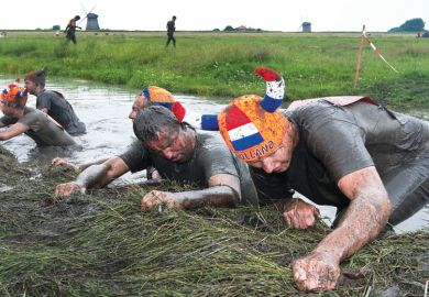 """Participants of the traditional mud marathon in Schermerhornon pulling themselves up as a metaphor for recognising """"team spirit"""""""
