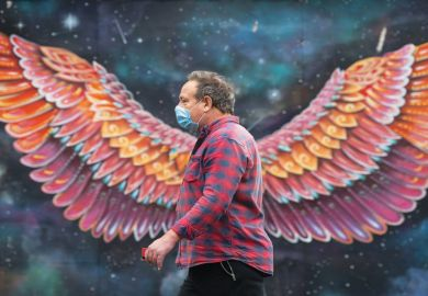 Man with a mask walks in front of wings painting on wall as a metaphor for Which Covid innovations should be embraced