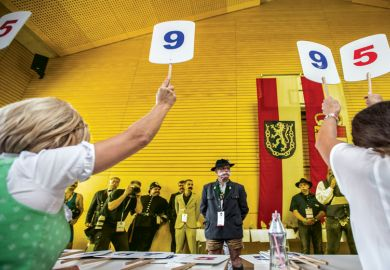 Contestants line up for judging panel who are holding up scores on boards as a metaphor for Discretion' has no place in determining degree classifications