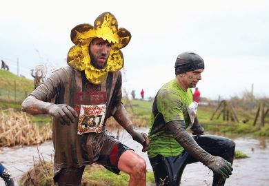 A competitor runs wearing a flower around his head covered in mud as a metaphor for UK 'needs coherent plan' for research spending after Horizon row.