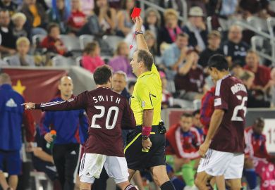 Referee delivers a red card sending a player off as a metaphor for rejection to both to the universities and the applicants.