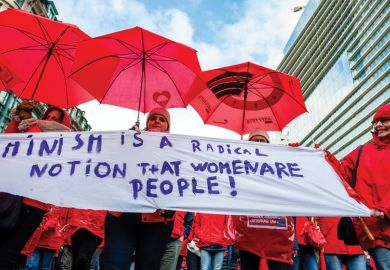 A group of women are holding a feminist placard while holding red umbrellas, during the National demonstration for better social security, in Brussels