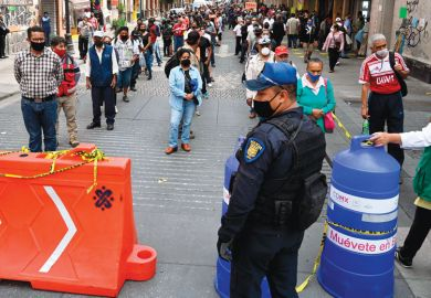 Police and city government workers stand at a pedestrian control that limits the access in groups of 20 people to enter downtown Mexico City