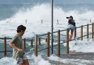 Two boys are seen avoiding large waves washing through the closed ocean pool at Dee Why Point, Sydney, Australia