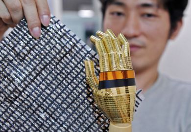 Tokyo University researcher shows a sheet containing carbon nano tubes and a robot hand