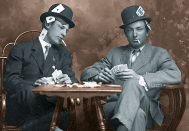 Two young men pretending to play cards. They are smoking and they sit close to a small table. Both men wear hats and have their legs crossed. One man is peeking into the other's card hand. Both guys have aces, kings and other cards visibly hidden in all p