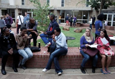 Students chat outside lecture halls at the University of the Free State in Bloemfontein, South Africa. Races are mixing more but often they socialize with their own kind.