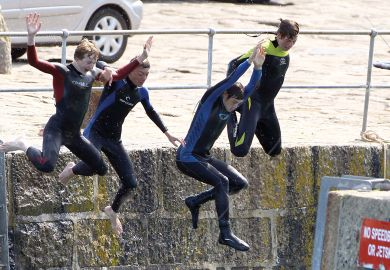 Four people jumping off from a harbour wall as a metaphor for cutting English fees and student numbers.