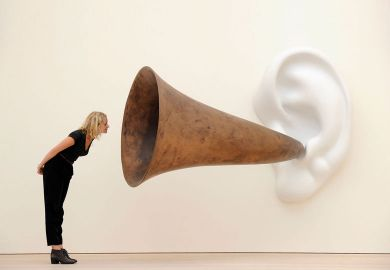 Woman leans in looking at an installation installation by US artist John Baldessari entitled 'Beethoven's Trumpet (With Ear)' as a metaphor for universities will 'listen to students'