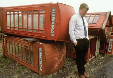 Person with  with old phone boxes for sale