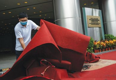 A man lifts a red carpet outside an Office