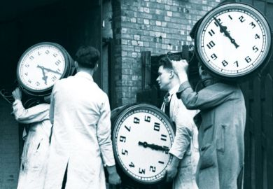 """Workers carrying large clocks as Traditional three-hour university exams may soon be a thing of the past as leading UK institutions eye a switch to online and more """"authentic"""" forms of assessment"""