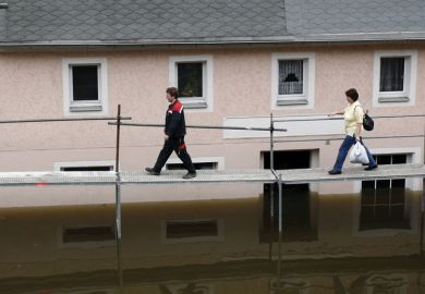 People walking on a tempory bridge in Germany as a metaphor for precariously employed German academics