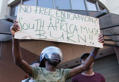 :Students stage a protest over government's plan of increasing university tuition feesi in front of the Parliament building in Cape Town, South Africa