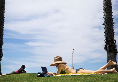 Person sunbathing in a bikini with her laptop