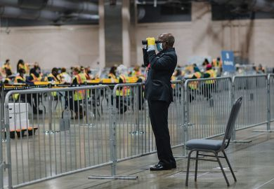 An official poll watcher uses binoculars as workers count ballots for the 2020 Presidential election.