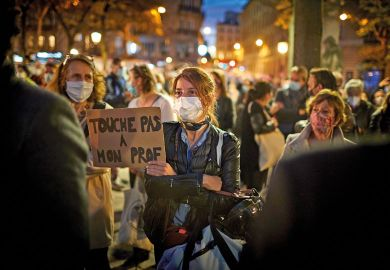 A member of the crowd watching the National Tribute to the murdered school teacher Samuel Paty holds a placard reading 'Do not touch my Professor' at Place de la Sorbonne on October 21, 2020 in Paris, France.