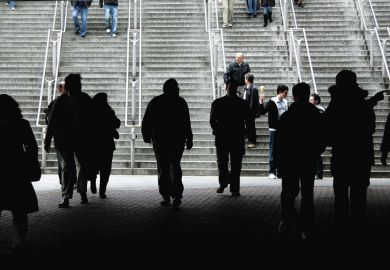 Silhouette of crowd walking towards stairs as a metaphor for more European staff leaving UK for universities abroad post-Brexit