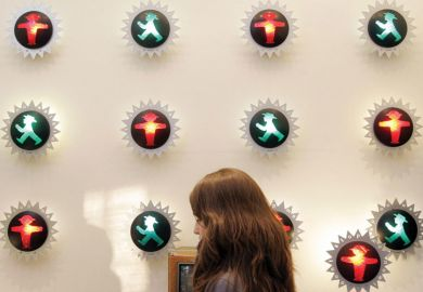 Person walking past a wall with an number of little traffic lights of red and green man in the centre of each as a metaphor for confused communication