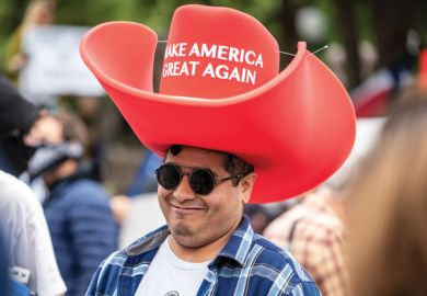 """A person wears an oversized """"Make America Great Again"""" hat as a metaphor for the US lawmakers to adopt philanthropic tactics for dictating academic content"""