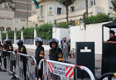 Egyptian security forces stand guard outside the Saudi embassy as a metaphor that a University of Washington doctoral student is being detained in Egypt.