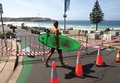 A surfer walks past the entrance to the car park to Bondi Beach which is blocked as a metaphor for research grant veto powers need guidance, say scholars