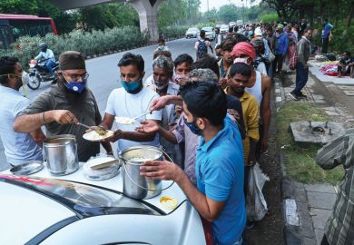 Homeless people queue for food along a road in New Delhi to show the hardship people have during Covid.