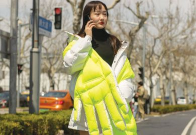 Lady wearing wearing neon quilted large hand design in Shanghai, China as a metaphor for a rigid system pushes Chinese students to use private agents.