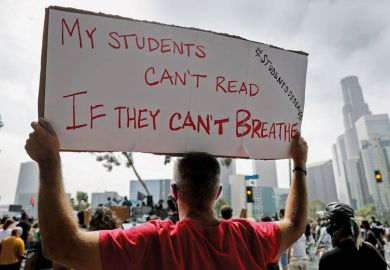 Protestor holding banner reading 'My students can't read If they can't breath for US college students battle alumni as they seek racial equity.