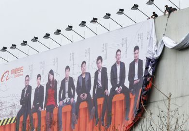 Two people setting up a large billboard of an image of a row of people sitting in a line at the Alibaba Group headquarters for Students seeing little benefit from Chinese start-up drive