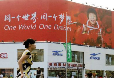 Person walking past a poster reading 'One World One Dream' in English and Chinese as a metaphor for Taiwan eyes international recruitment with switch to English.