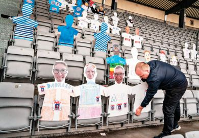 A man places cardboard figures with pictures of the fans in the empty tribunes of the Ceres Park Football Stadium