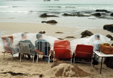 People on deckchairs shelter under plastic sheets on beach