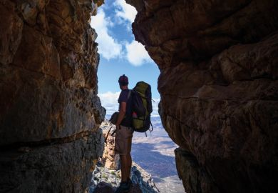 Hiker observes view from gap in rocks