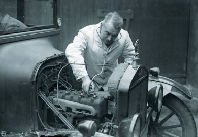 A motor mechanic listens to a car engine with a stethoscope.