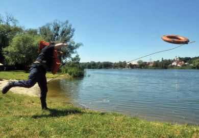 A rescuer throws a lifebelt into a lake