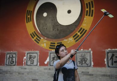 A tourist takes a selfie stick while visiting an ancient palace in China
