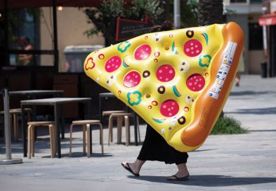 A woman carries an inflatable float with the shape of a portion of pizza
