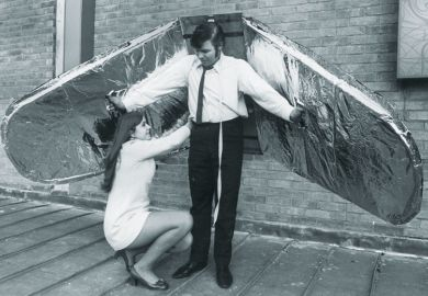 Woman helps a man who prepares for an attempt to fly, using wings made from balsa wood