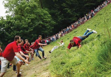 a competitor comes tumbling down the hill during the cheese rolling competition near the village of Brockworth, Gloucester, in western England