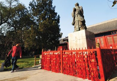 A man walking past looks at a statue of Chinese philosopher Confucius