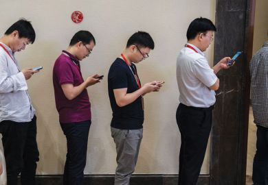 row of men  look at their smartphones