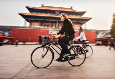 Friends riding retro bicycles along forbidden city