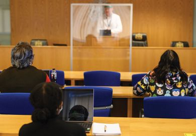 ecturer Ian Bowden teaches law students wearing face coverings to help mitigate the spread of the novel coronavirus .