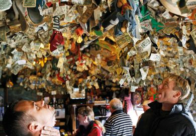 People looking up at pinned mementos left on the ceiling.