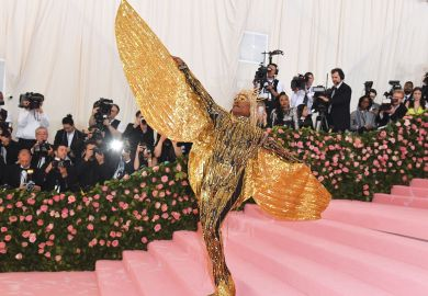 on the red carpet person wearing  huge gold sparkle angel wings