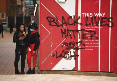 two people stand stand beside Black Lives Matters graffiti